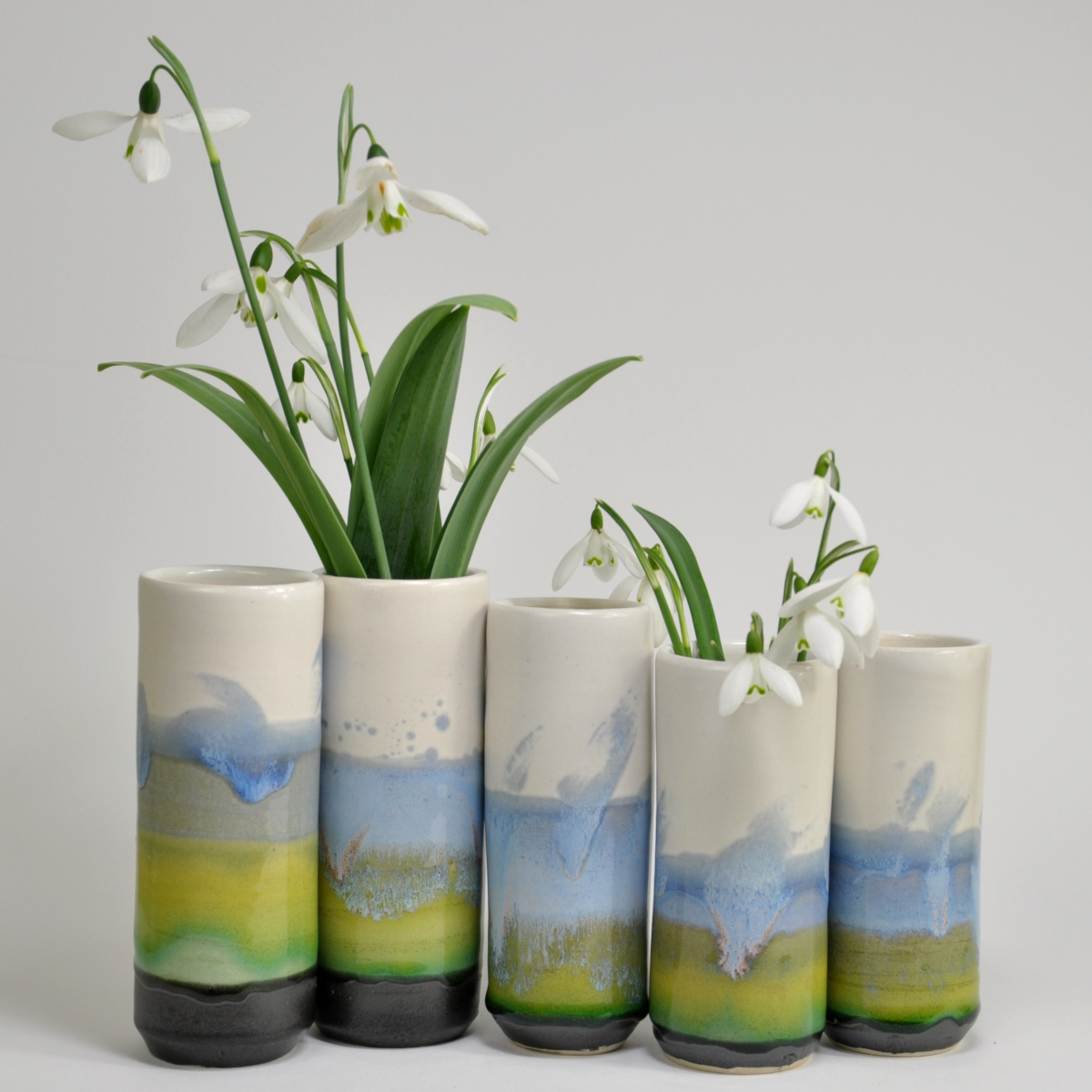 glossy blue green and satin white windowsill vases with snowdrops
